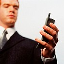 Low angle view of a businessman looking at a mobile phone