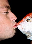 Close-up side view of a young man kissing a fish