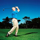 Side profile of an elderly man teeing off on golf course