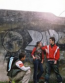Young woman talking to two young men against a wall