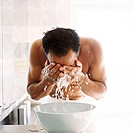 Close-up of a young man washing his face in a basin of water
