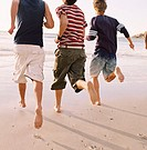 Rear view of three young men running at the beach