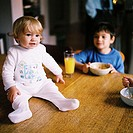 Baby (12-18 months) sitting on the breakfast table