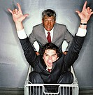 Portrait of an elderly businessman pushing a young businessman in a shopping cart