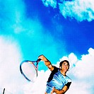 Low angle view of a young man playing tennis