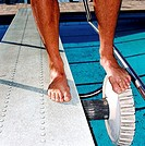 Close-up of the feet of a male swimmer adjusting flexibility on a diving board