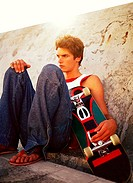 Young man sitting against a wall holding a skateboard
