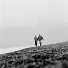 Man and woman holding hands and walking at the beach (Black and white)