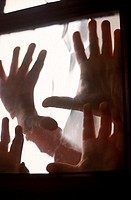 Close-up of human hands on the glass of a window