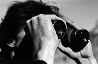 Young man looking through binoculars (black and white)