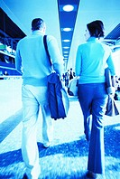 Rear view of a young couple walking in an airport (toned)