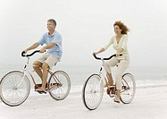 Mature couple riding bikes on beach