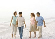 Two mature couples walking on beach, holding hands