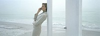Woman leaning against doorframe on beach, using cell phone