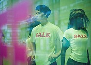 Mannequins in shop window wearing sale tee-shirts