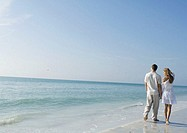 Couple walking alongside water on beach