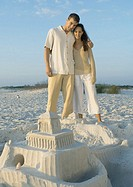 Couple standing on beach looking at sand castle