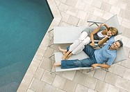 Mature couple lounging by pool