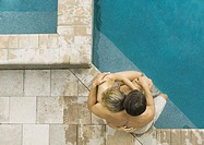 Couple sitting on edge of pool together