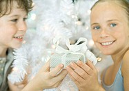 Boy handing sister gift in front of christmas tree