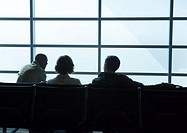 Silhouette of travelers in airport lounge