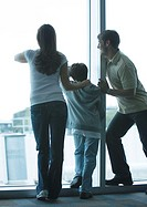 Family looking through window in airport