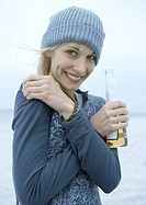 Young woman holding beer bottle on beach