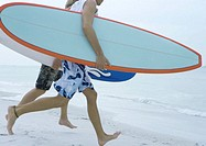 Young men running with surfboards