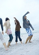 Young adult friends dancing on beach