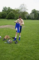 Footballer getting changed in the park