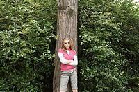 Teenage girl standing against a tree