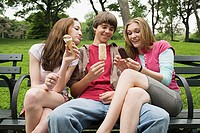 Three teenagers eating ice cream