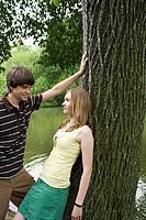 Teenage couple flirting near a tree