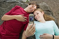 Teenage couple using a camera telephone
