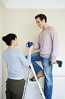 Woman handing coffee to husband on stepladder