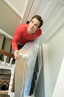 Man on stairs with a mattress