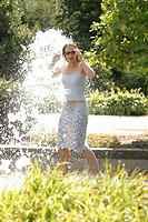 Young woman takes summerly refreshment by a fountain.
