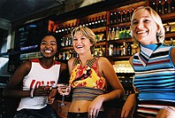 low angle view of three woman sitting at a bar counter and smiling