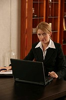 A blonde businesswoman working on her laptop in her office.