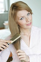 A blonde woman straightens her hair as she looks at the camera