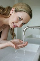 A blonde woman holds water in her palms as she smiles at the camera.