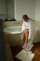 A blonde woman cleaning her foot.