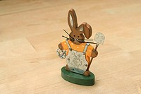 A wooden rabbit figure holding a shovel and a basket.