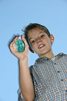 Low angle view of a young boy holding a green colored yoyo.
