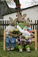 A family of dummy rabbits is decorated on the bench on an event.