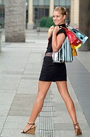 Young woman holding shopping bags outdoors, looking over shoulder
