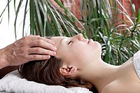 Young woman getting massage, eyes closed, side view.
