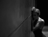 Young woman with bare arms leaning against wall, blurred, b&w