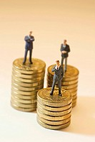Miniature Businessmen on Stacks of Coins