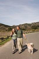 Couple Walking Their Golden Retriever